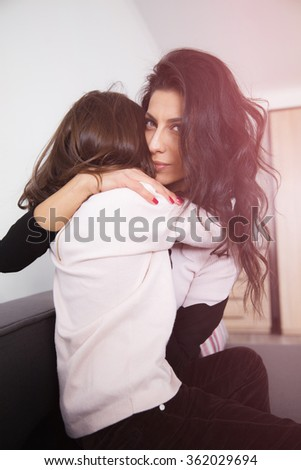 Young mother and her daughter sitting on the sofa and hugging at home in white lit room against the window. Smooth morning light, casual style - concept of happy family living and lifestyle - stock photo
