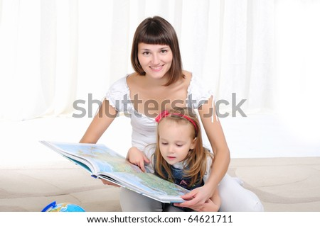 Young mother and her daughter studying geography with atlas