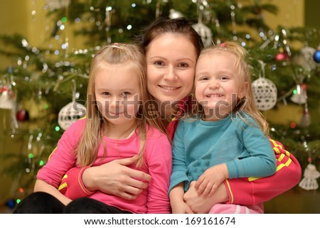 Young mother and her daughters on Christmas  - stock photo