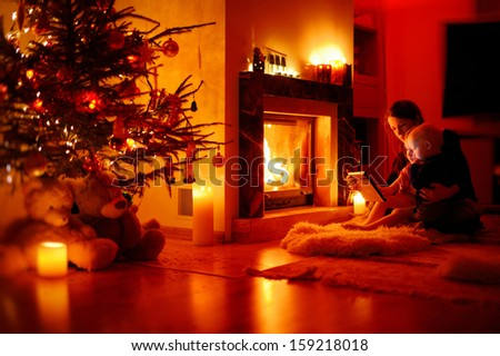 Young mother and her daughters using a tablet pc by a fireplace - stock photo