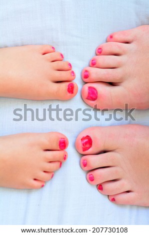 Young mother (30) and her girl child daughter (4 years old) compare the size of their painted nail polish feet. - stock photo