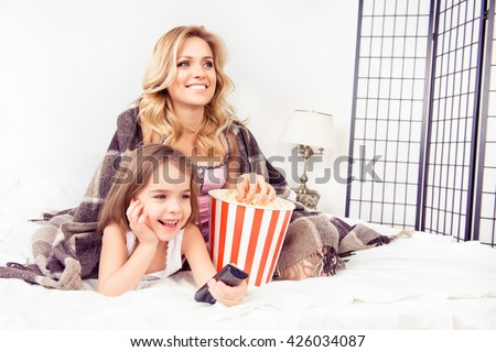 Young mother and her happy child watching tv with popcorn