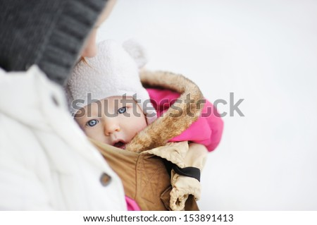 Young mother and her little baby in a carrier at winter