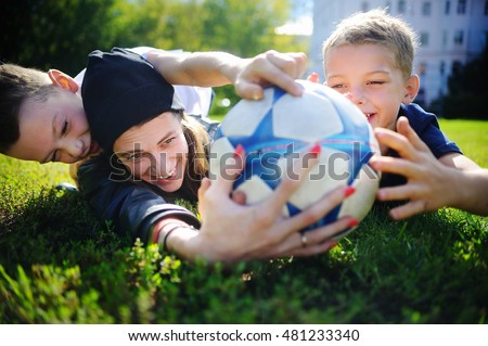 Young mother and her little boys playing a soccer game on sunny summer day. Family having fun with ball outdoors