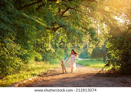 Young mother and her little cute son walking in the park at sunset holding hands. - stock photo
