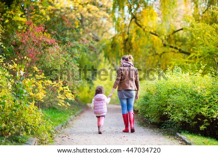 Young mother and her little daughter at beautiful autumn park. Kid girl and beautiful woman in gumboots walking and having fun. Family portrait outdoors.