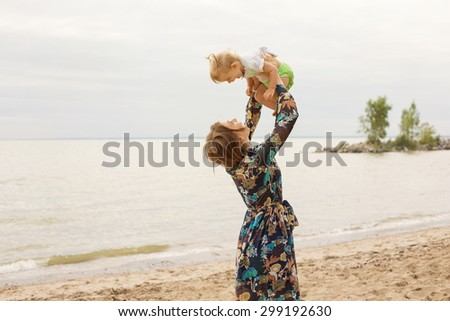 Young Mother and her Little Daughter Baby Outdoor Playing on the Beach near Sea. Family Love Concept - stock photo
