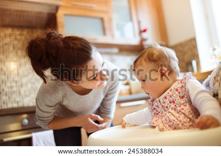 Young mother and her little daughter having breakfast together - stock photo