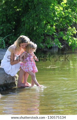 young mother and her little daughter squirt water at the lake