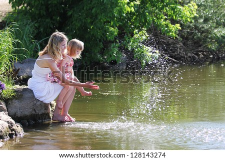 young mother and her little daughter squirting water at the lake