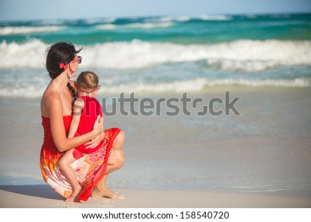 Young mother and her little daughter walking on tropical beach