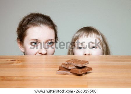 Young mother and her little daughter wanting to eat milk chocolate, neutral background - stock photo