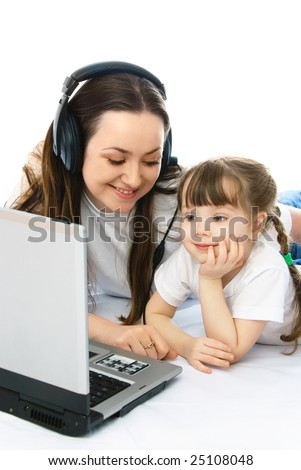 young mother and her little daughter with a laptop on the floor