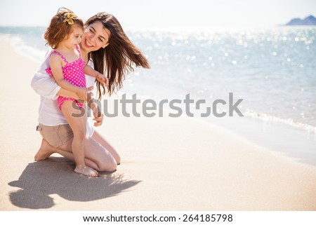 Young mother and her little girl enjoying the ocean view and relaxing at the beach on a sunny day - stock photo