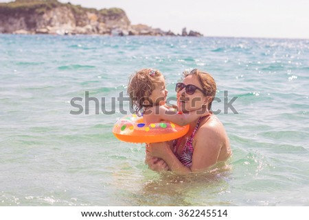 Young Mother and her little girl have fun in the beautiful  sea on summer day. Travel Vacation lifestyle. - stock photo