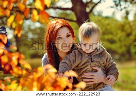 Young mother and her little girl in autumn
