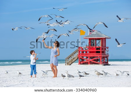Young mother and her little son feeding seagulls on tropical beach, Florida summer holiday vacation - stock photo