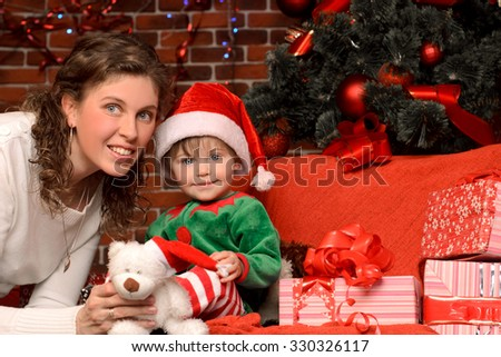 young mother and her little son in suit and hat in christmas interior in red