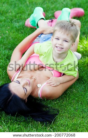 Young mother and her little son outdoors in colorful rubber boots