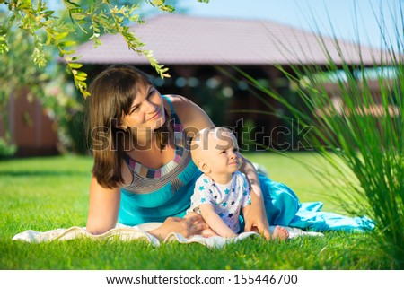 Young mother and her little son resting on grass  - stock photo