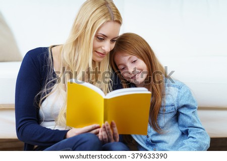 Young mother and her pretty little redhead daughter reading a book together on a sofa with their heads close together