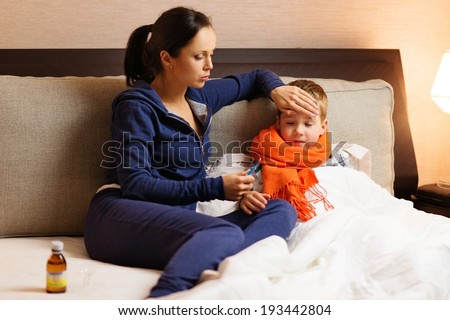 Young mother and her sick son in a bed - stock photo