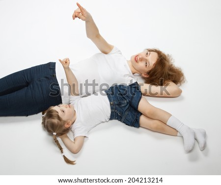 Young mother and her smiling little daughter lying on the floor - stock photo