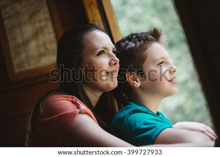 Young mother and her son enjoys traveling by old steam train. They looks through the open window and smiling. Photo was edited to match old film look.