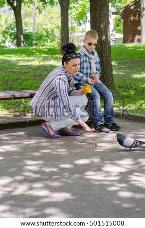 young mother and her son feeding pigeons in the park