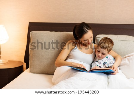 Young mother and her son reading book in a bed  - stock photo
