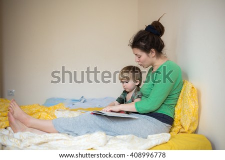 Young mother and her son toddler reading book in a bed casual lifestyle photo series in real life interior - stock photo