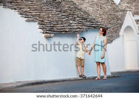 Young mother and her son walking narrow streets ot typical italian town, Alberobello, Italy - stock photo