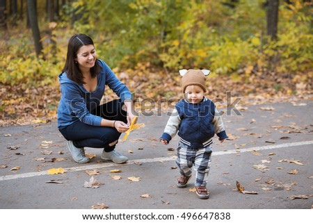 Young mother and her toddler baby boy have fun in autumn park with falling leaves. Happy fa,ily concept. Mom with her years old son walking outdoors in autumn