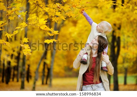 Young mother and her toddler girl have fun at autumn - stock photo