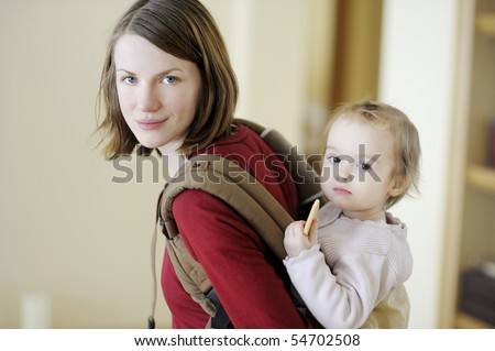 Young mother and her toddler girl in a baby carrier - stock photo