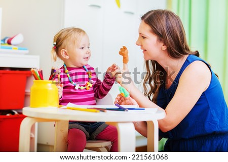 Young mother and her toddler girl playing together with finger toys - stock photo