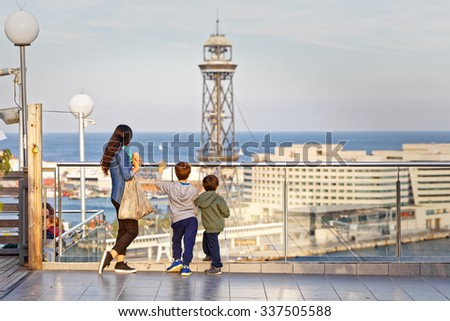 Young mother and her two children contemplate the view from the top of the Port of Barcelona from a terrace - stock photo