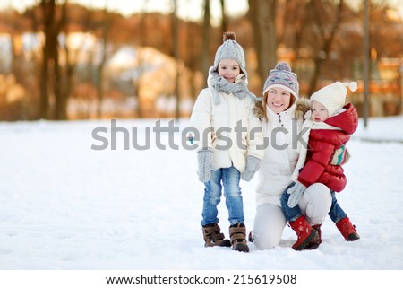 Young mother and her two daughters having fun on winter day - stock photo