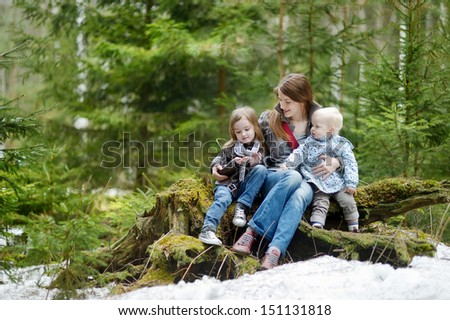 Young mother and her two daughters outdoors on beautiful day