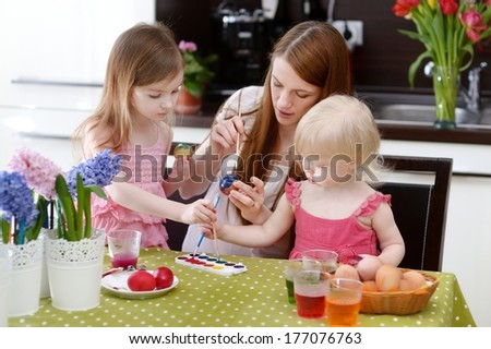 Young mother and her two daughters painting Easter eggs