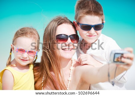 Young mother and her two kids taking self portrait with compact camera