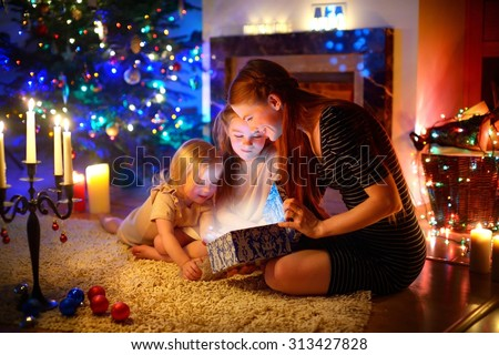 Young mother and her two little daughters opening a magical Christmas gift by a Christmas tree in cozy living room in winter - stock photo