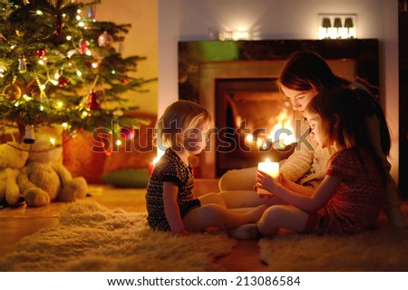 Young mother and her two little daughters sitting by a fireplace holding a candle in a cozy dark living room on Christmas eve - stock photo
