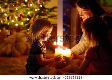 Young mother and her two little daughters sitting by a fireplace holding candles in a cozy dark living room on Christmas eve - stock photo