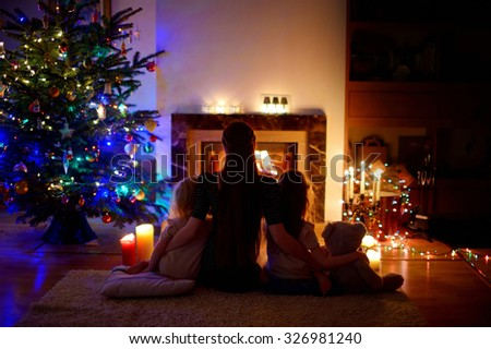 Young mother and her two little daughters sitting by a fireplace in a cozy dark living room on Christmas eve - stock photo