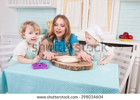 Young mother and her two small daughters in the kitchen - stock photo