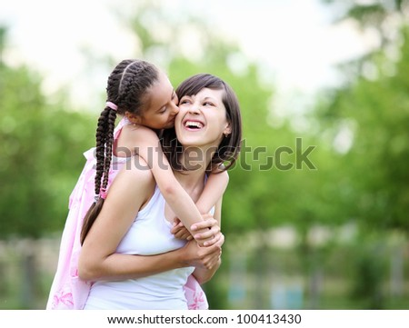 Young mother and her young daughter fun time together outdoors. - stock photo