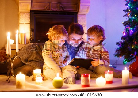 Young mother and his two little children sitting by a fireplace at home on Christmas time. Kids boys playing with tablet. Through window from outdoors