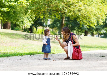 Young mother and little daughter of one year walking through summer park