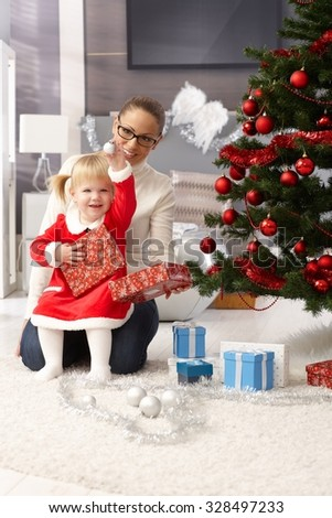 Young mother and little daughter opening presents under christmas tree.